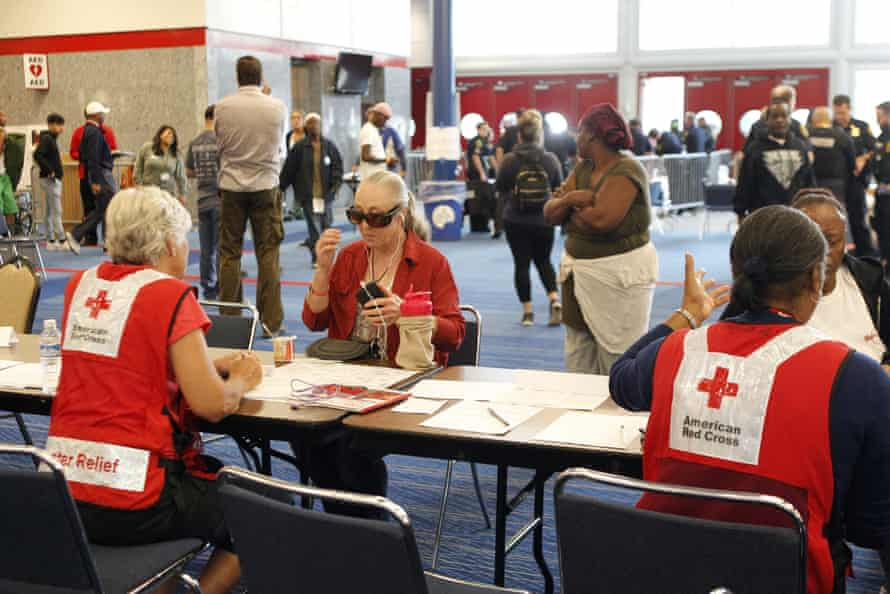 Members of the Red Cross help people register at George Brown Convention Centre, which has been opened as a shelter in Houston, Texas