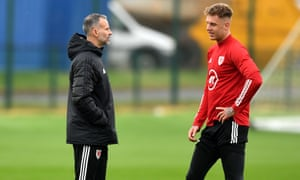 Ryan Giggs, the Wales manager, talks to Joe Rodon, the Swansea defender who was the subject of an inquiry from Tottenham this week.