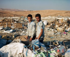 Brothers Ahmed and Mahmoud of Yatta village, near Hebron, collect metal scraps at the nearby landfill in hopes to sell it for a small profit. They are wearing Israeli police shirts found in the trash.