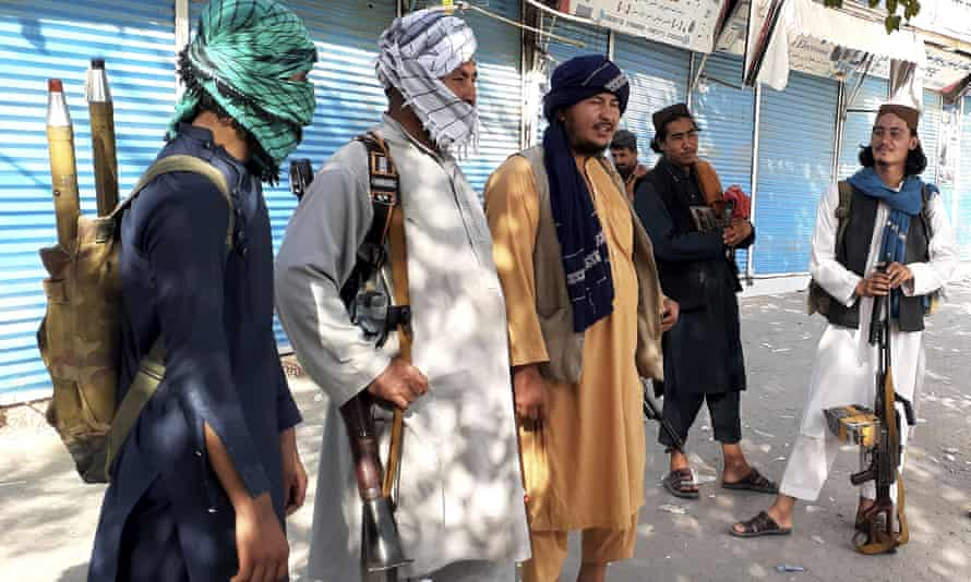Taliban fighters stand guard in Kunduz after capturing the strategic city in northern Afghanistan on Sunday