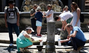 Tourists in Rome drink from a public fountain during the unusually early summer heatwave.