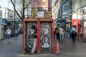 A man counts his money while standing in a phone booth in Brixton