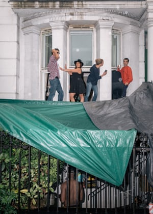 Soleme (wearing a black hat) dances on her windowsill with friends, whilst a neighbour gets drinks from a basement, during a rainy start to the Notting Hill Carnival on Sunday. Soleme has lived here for about a year and works in a pub locally.