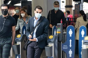 Commuters wearing face masks walk through the ticket barriers at Waterloo Station in London on June 15, 2020.