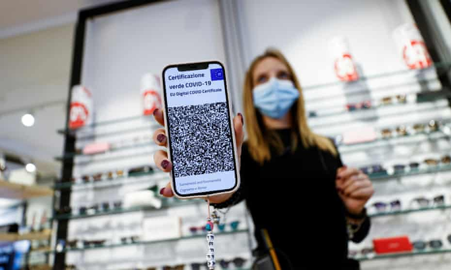 An employee at an optician shop shows her Covid-19 'green pass' a day before it becomes obligatory for all workers either to show proof of vaccination, a negative test or recent recovery from infection to access their workplaces.