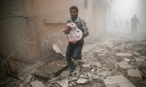 A Syrian man carries a baby wrapped in a blanket following airstrikes on the town of Douma, a rebel stronghold east of Damascus