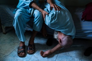 An elderly man falls from his bunk at the Helmand Drug Addict's Treatment Center in the provincial capital, Lashkar Gah.