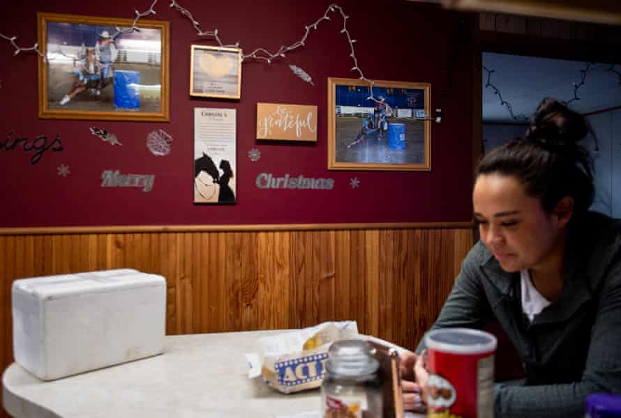 Photos of Simonson and her sister, Kiana Simonson, from recent barrel races hang on a wall in their Missoula home as Keira video chats with a friend from the UM rodeo team.