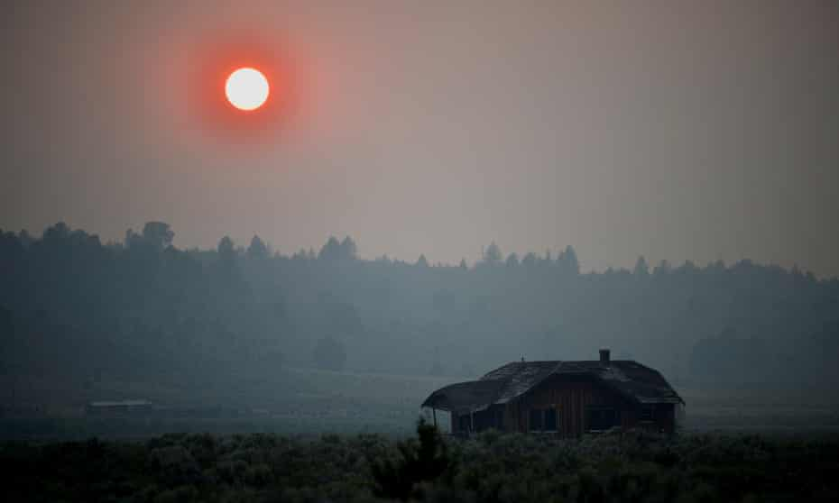Thick smoke causes the sun to glow red over an abandoned farmhouse as the Bootleg fire expands near Beatty, Oregon.