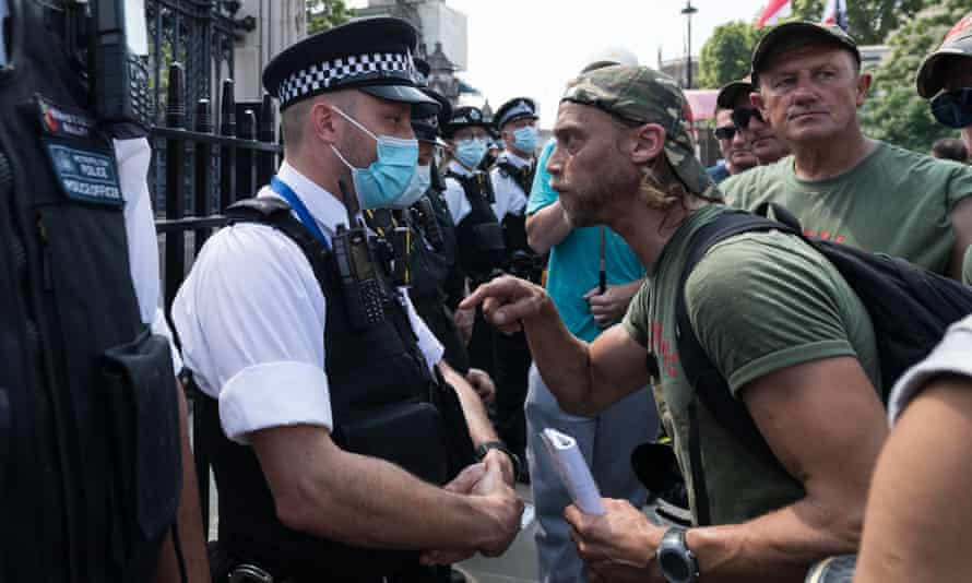 A man confronts a police officer during a protest against Covid-19 measures and vaccines in London.