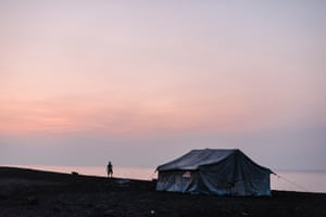 A man watches the sun set over Ambae Island. Communities from villages in the mountain were provided with tents for temporary housing when they evacuated to safer ground along the coastline in April due to volcanic activity.