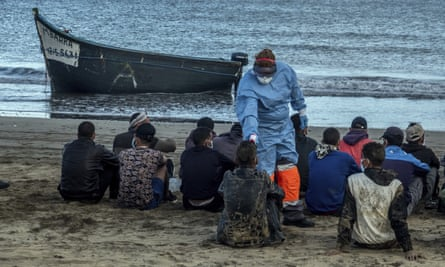 Migrants from Morocco have their temperature checked by an official after landing in the Canary Islands.