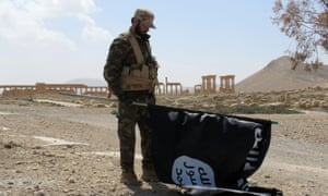 A Syrian government soldier with a captured Islamic State flag in Palmyra, Syria, March 2016.