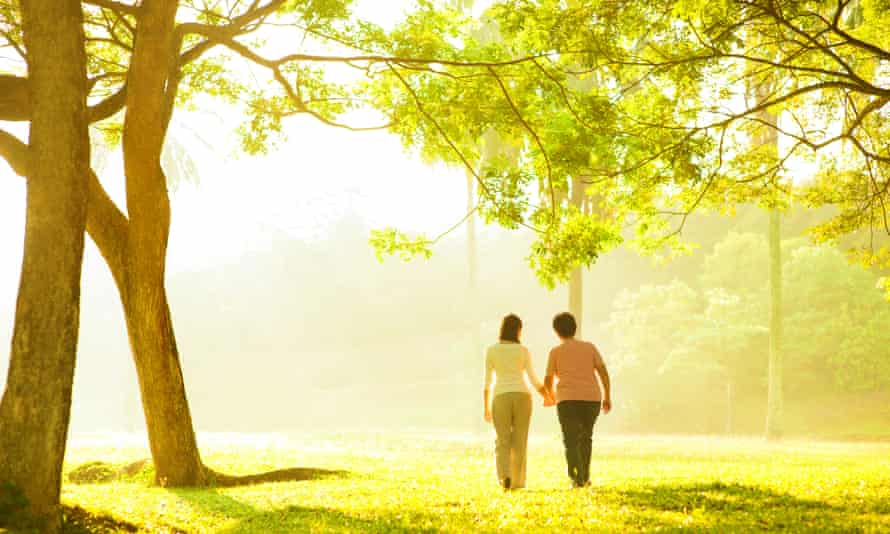 Asian familyAsian senior mother and adult daughter holding hands walking at outdoor park
