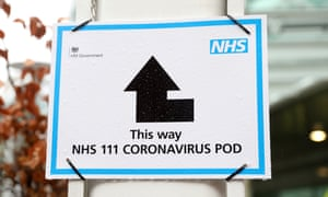 A sign directs patients towards an NHS 111 coronavirus pod outside University College hospital in London.