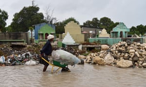 A woman pushes a wheelbarrow while walking in a partially flooded street in the Haitian capital, Port-au-Prince, on 4 October.
