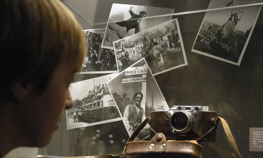 a visitor observes a Leica camera from Agusti Centelles and some of his pictures part of the exhibition Journey to a War. George Orwell in Catalonia and Aragon