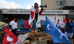 Medics demonstrate next to outdated equipment they have stored outside a hospital in Paris
