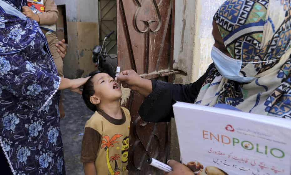 A health worker gives a polio vaccine to a child in Karachi, Pakistan, September 2020.