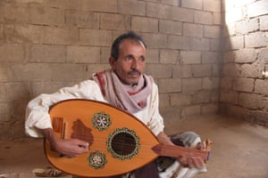 Ali sits with his lute, in the bare room now he rents for his family to live in since their own home was destroyed.
