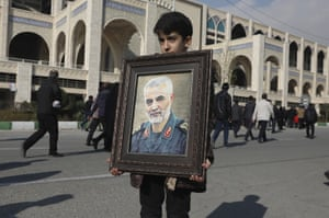 A boy carries a portrait of Iranian Revolutionary Guard Gen. Qassem Soleimani prior to the Friday prayers in Tehran, Iran.