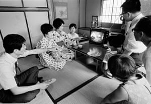 A Japanese family in Tokyo watch an image of President Richard Nixon superimposed on a live TV broadcast of the Apollo 11 astronauts salute from the Moon