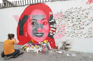 A woman kneels in front of a mural of Savita Halappanavar in Dublin
