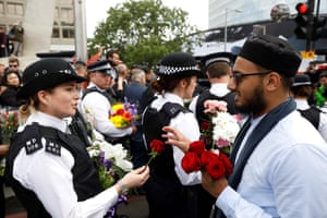 London, England A man hands a flower to a police officer
