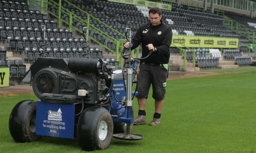 The groundsman, Adam Witchell, prepares the New Lawn pitch, which hosts its first Football League game on Saturday.