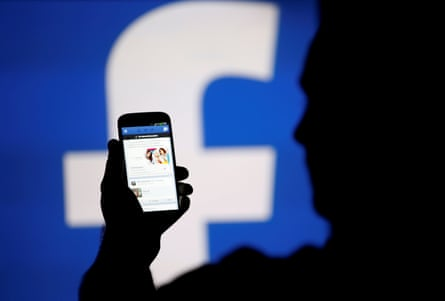 A man silhouetted against a video screen with a Facebook logo