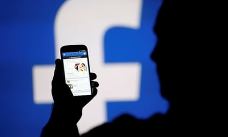 Silhouetted man holds phone in front of Facebook logo