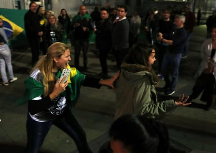 A supporter of presidential candidate Jair Bolsonaro pushes a woman during a protest after he was stabbed at Paulista avenue.