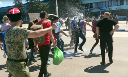 Film still showing Cossacks throwing milk at opposition leader Alexei Navally at Anapa airport.
