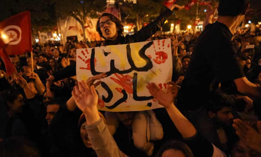 A young woman raised on a protester's shoulders holds a placard which reads, We are all Bardo