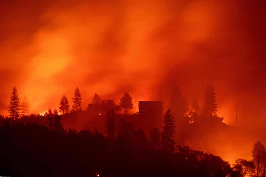 Flames from the Camp fire burn near a home atop a ridge near Big Bend, California.