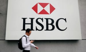 FILE PHOTO: A man walks past a logo of HSBC at its headquarters in Kuala Lumpur, Malaysia.