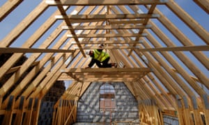 A builder surveying the roof timbers of a new house under construction