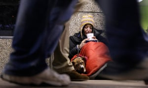A homeless woman from north Wales, sits huddled under a sleeping bag next to her dog Casper in a shopping arcade near the Victoria rail station in central London.