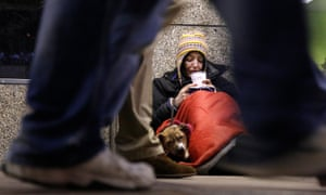 A homeless woman sits huddled under a sleeping bag next to her dog in London.