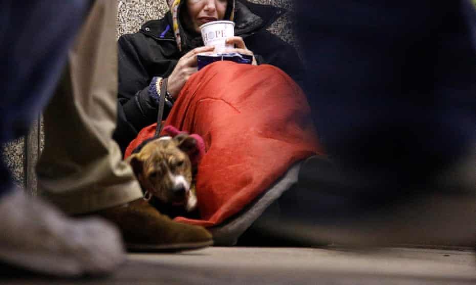 A homeless woman sits as pedestrians pass by