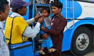 A child is vaccinated near buses in Pakistan