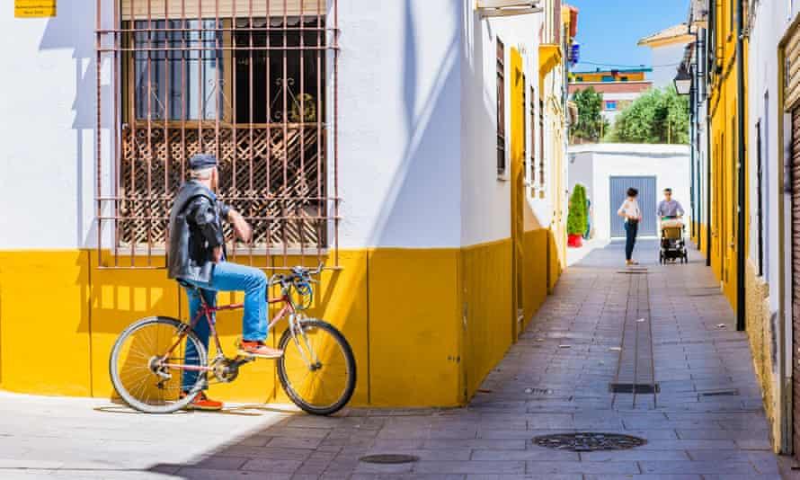 Man cycling talks through the bars of a window. Cordoba,