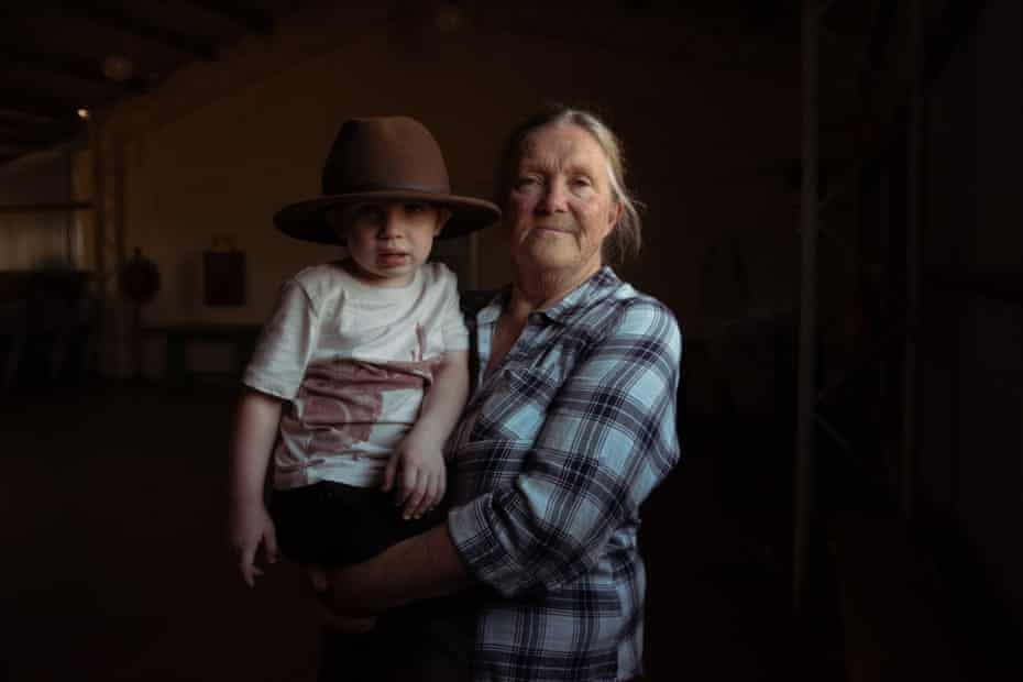 Resident Bev Smiles, 66, with her grand nephew, Will, 2, standing inside Wollar's memorial hall, once a lively meeting place for the community in country NSW.