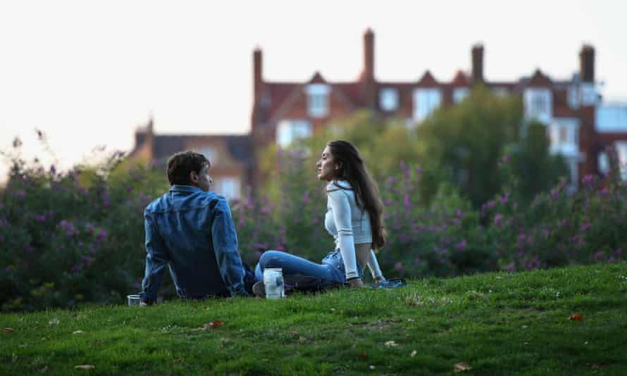 Young man and woman sit on grass in city park