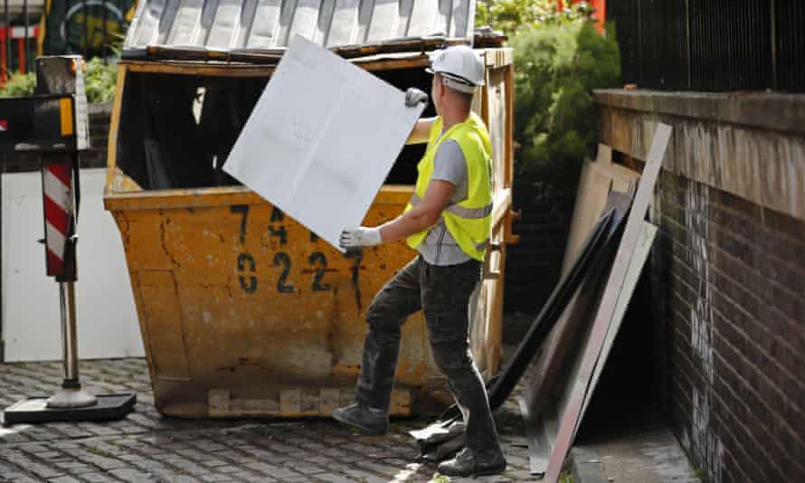 Worker disposes of cladding panels
