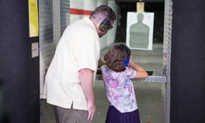 Pastor and NRA firearms instructor John offers guidance to his 8-year-old daughter Abby at the gun range