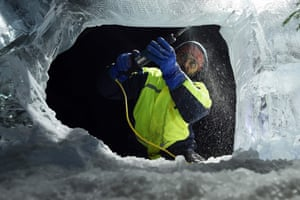 An ice sculptor works on a piece for the exhibition, rugged up against the cold