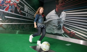 A young girl takes a penalty kick in the penalty shootout zone at Manchester's National Football Museum, UK.