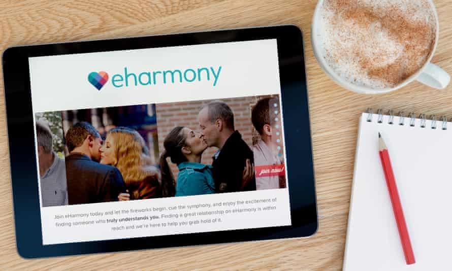 The eharmony website on an iPad on a wooden table beside a notepad.