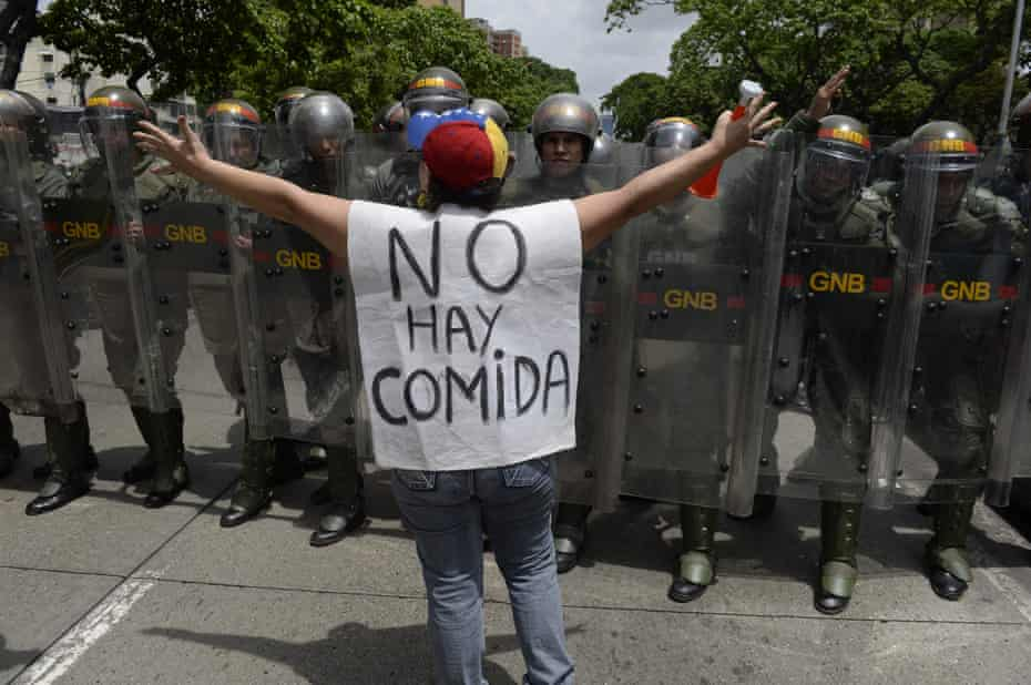 """A woman with a sign reading """"There is no food"""" protests against new emergency powers decreed by President Maduro in front of a line of police officers."""